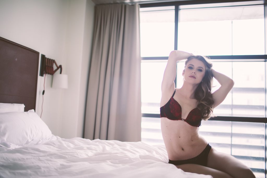 A beautiful woman in bed wearing red lingerie