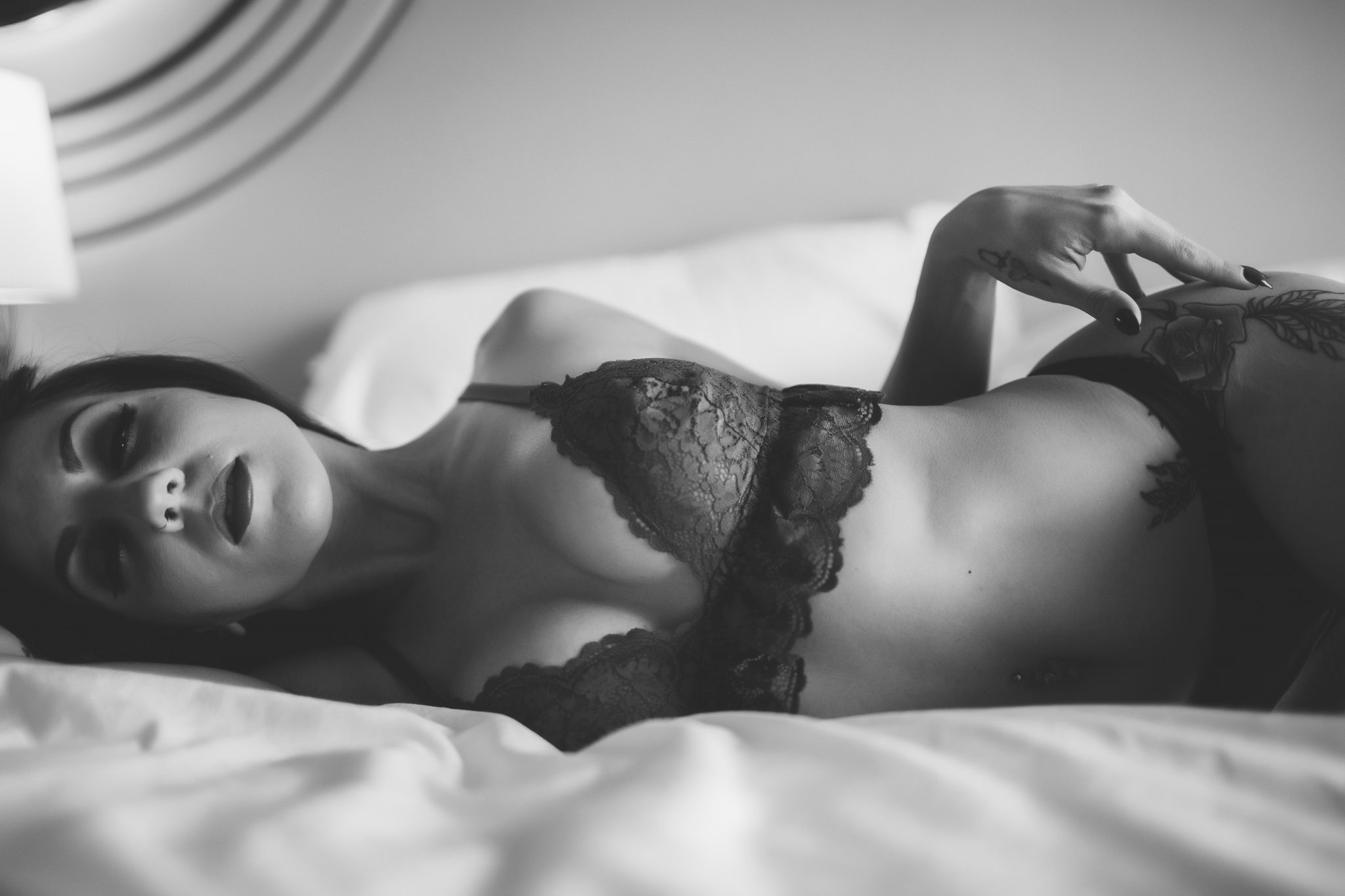 Tattooed model wearing lingerie and laying on bed