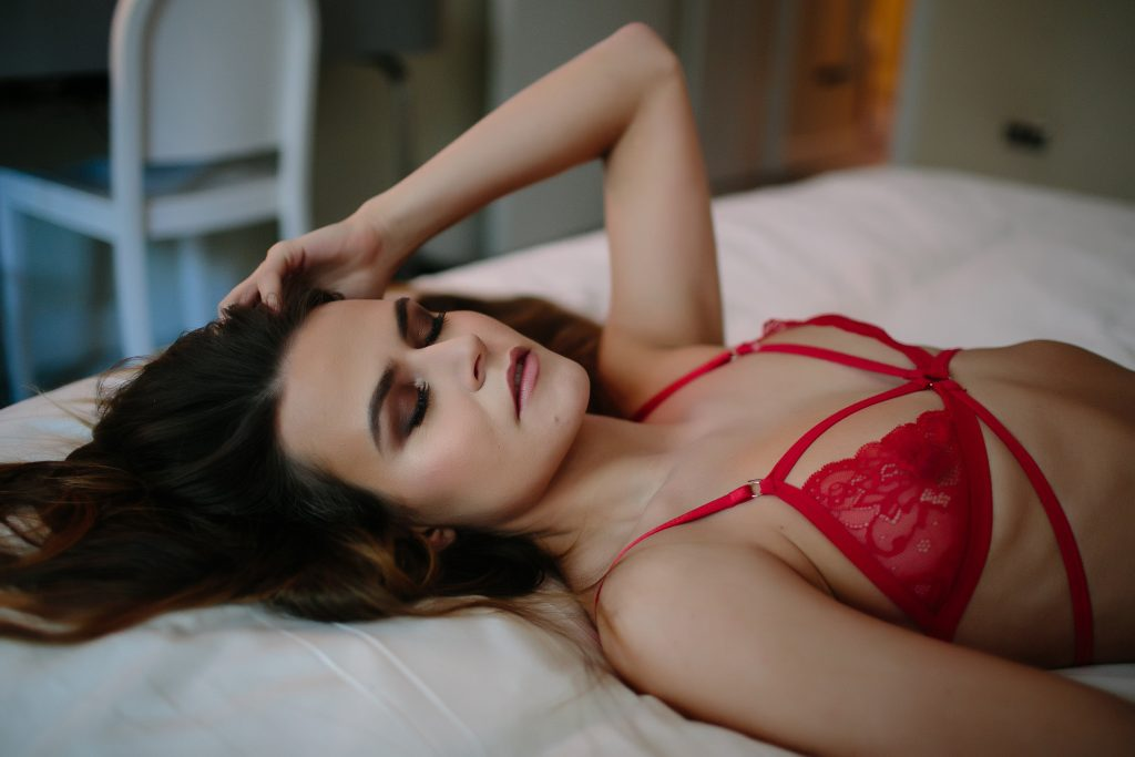 A woman wearing a red bra and posing for intimate photos