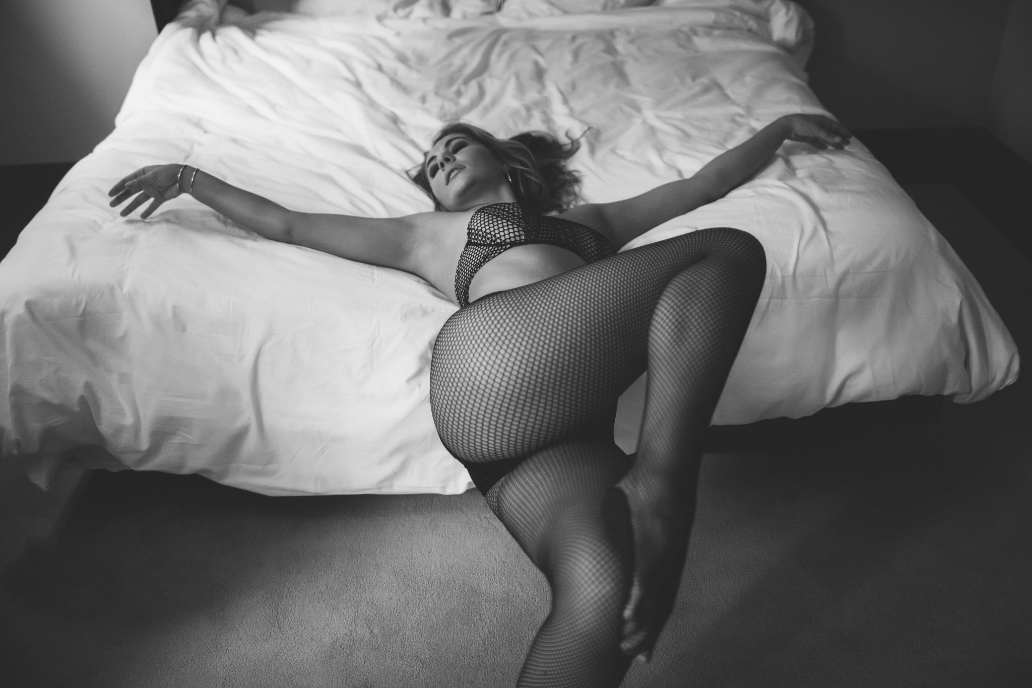 A woman wearing fishnet lingerie in a dramatic boudoir pose