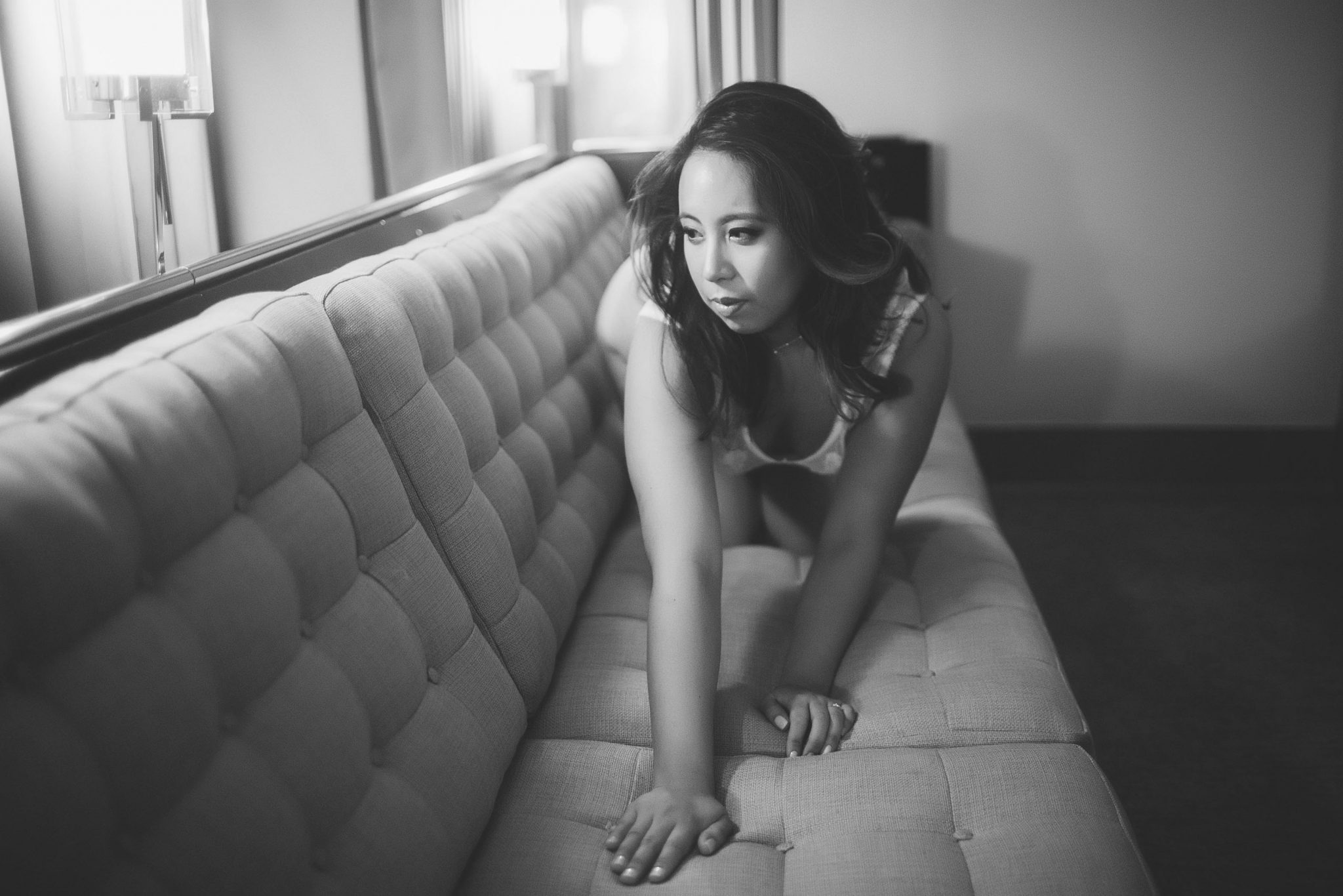 A woman wearing lingerie and posing on a couch