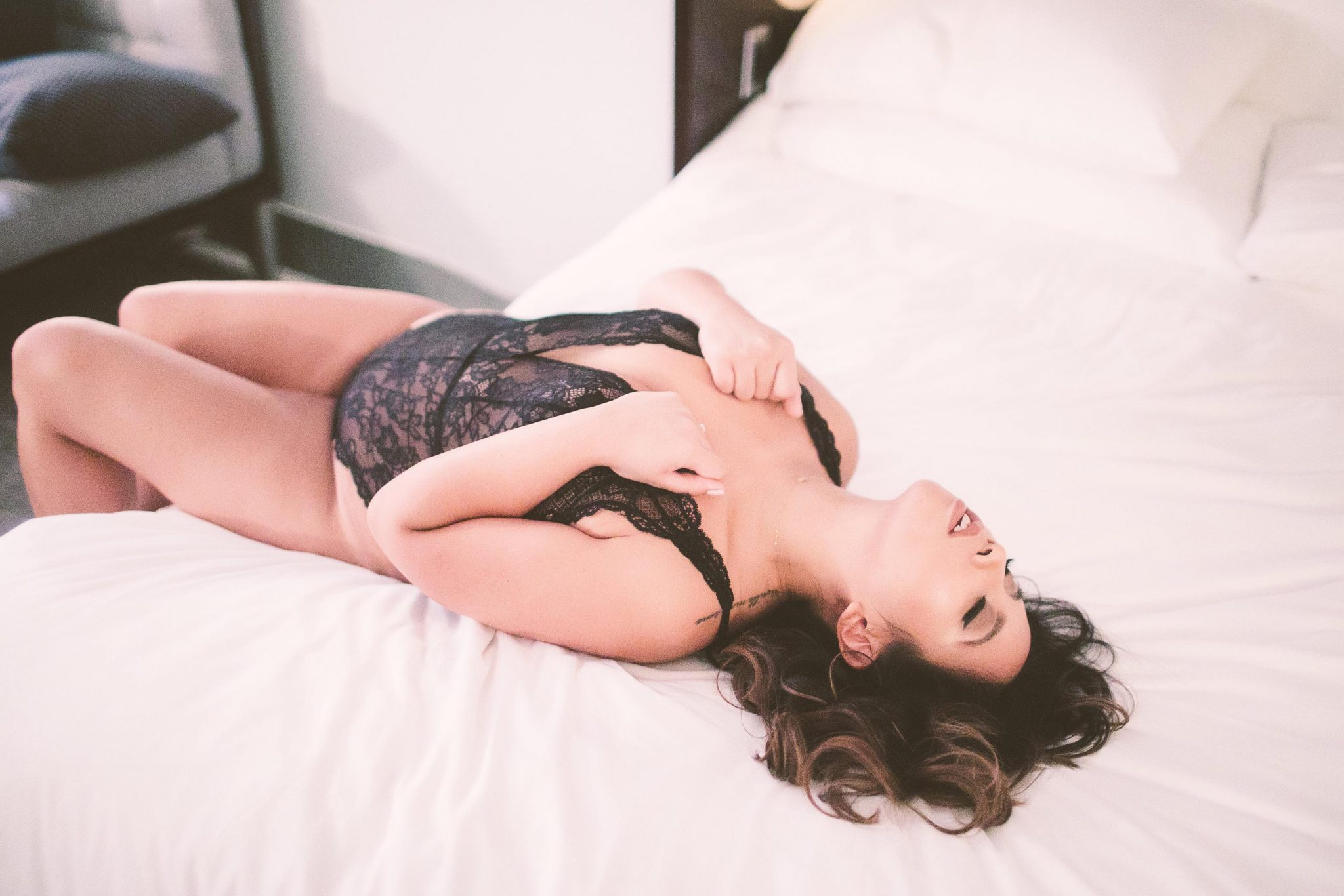 A boudoir model posing on a bed