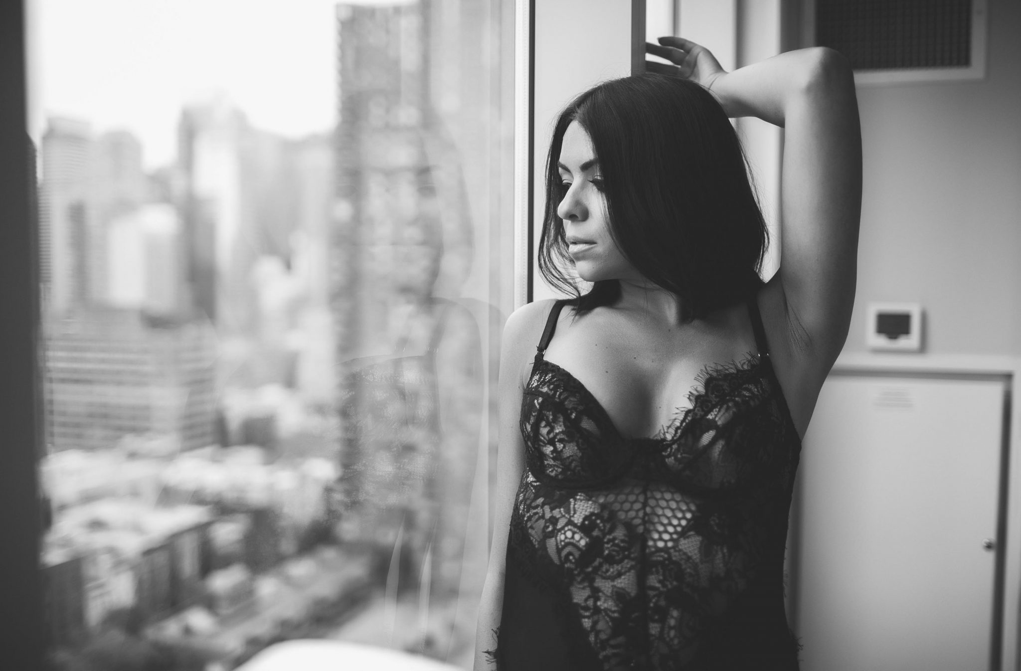 A woman in lingerie staring out the window at NYC