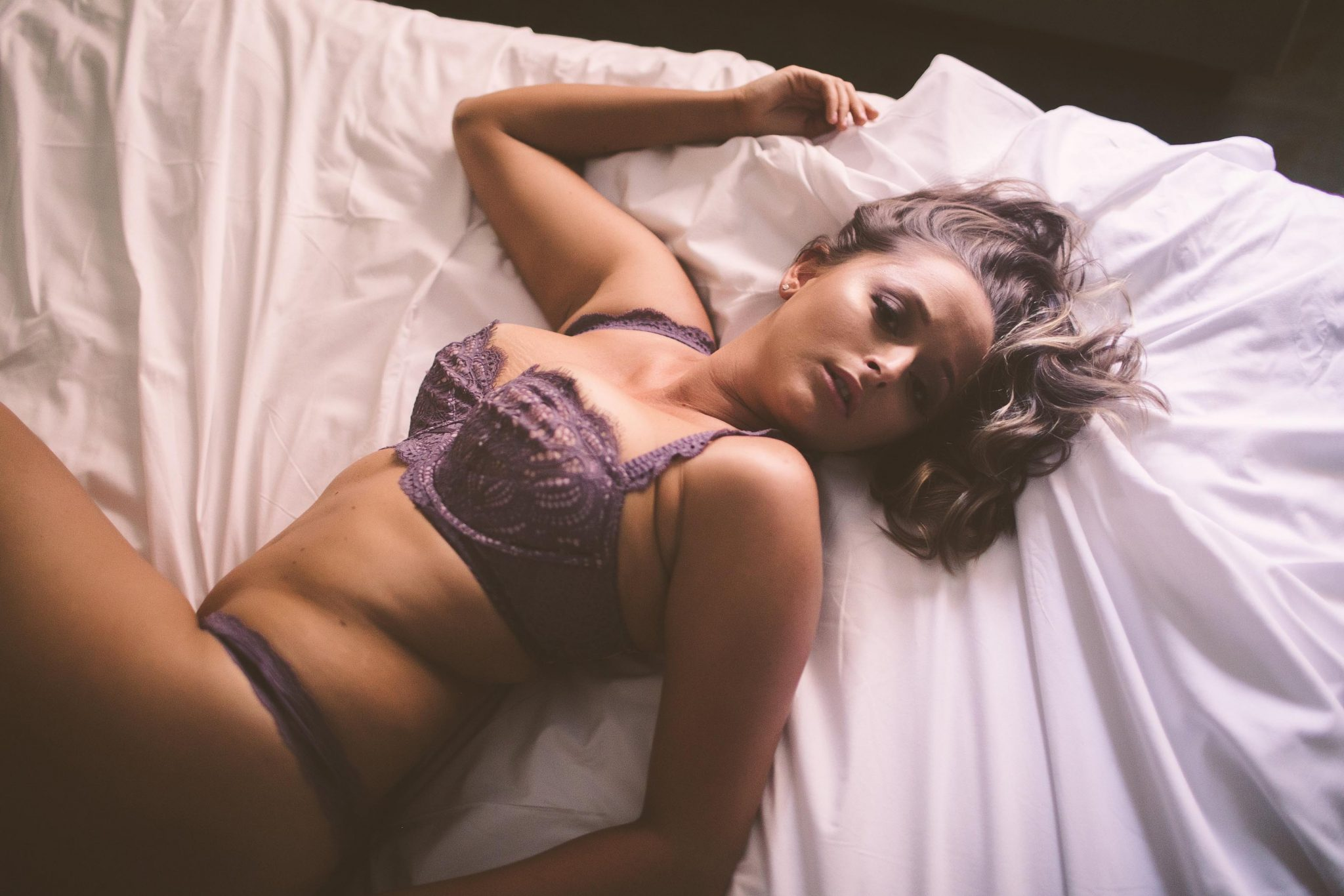 A lingerie model laying on a bed in a sexy boudoir pose