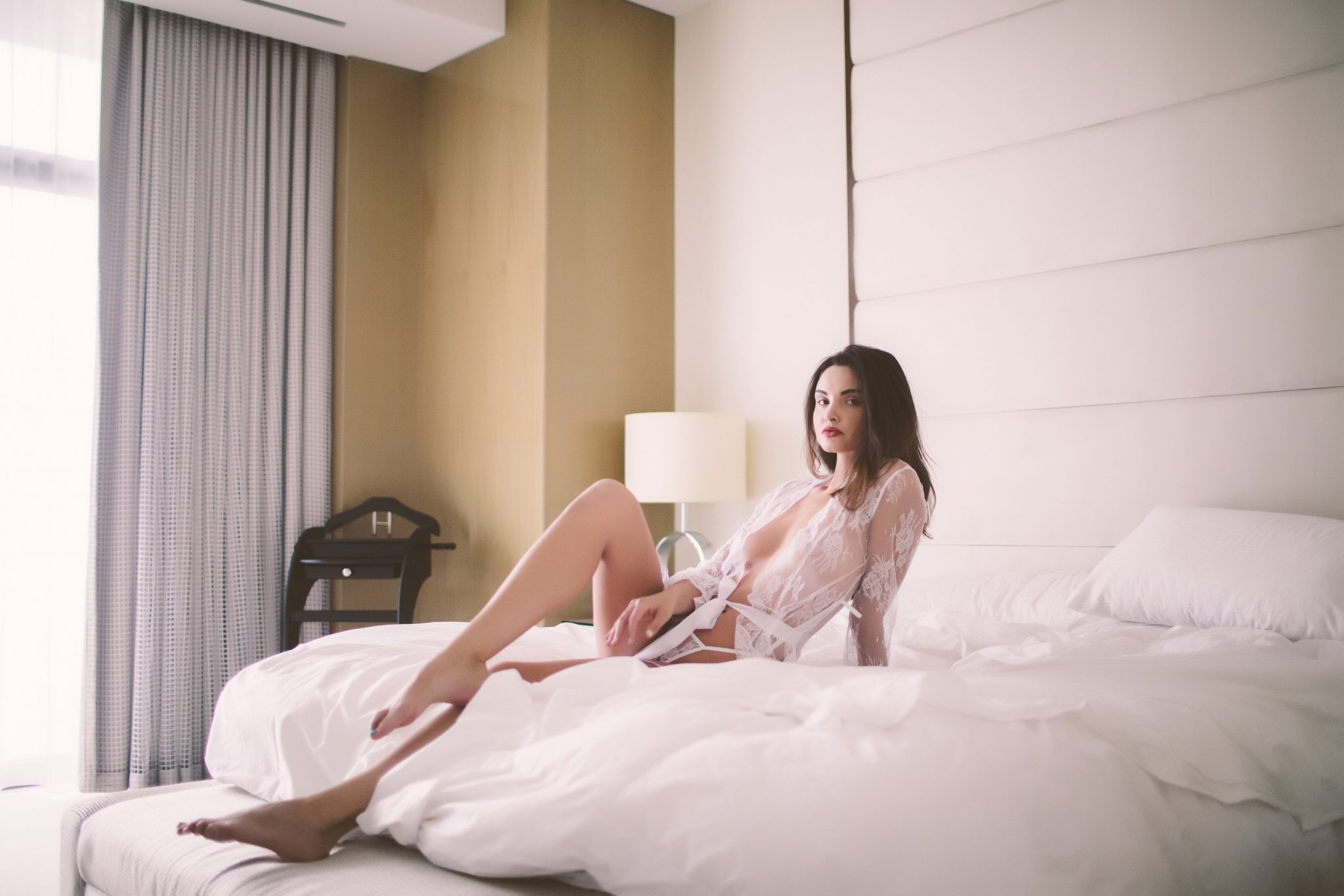A woman posing in a NYC hotel for a boudoir photo shoot