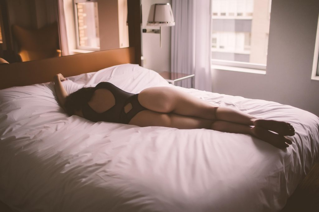 A woman posing on a NYC hotel bed during a boudoir photoshoot