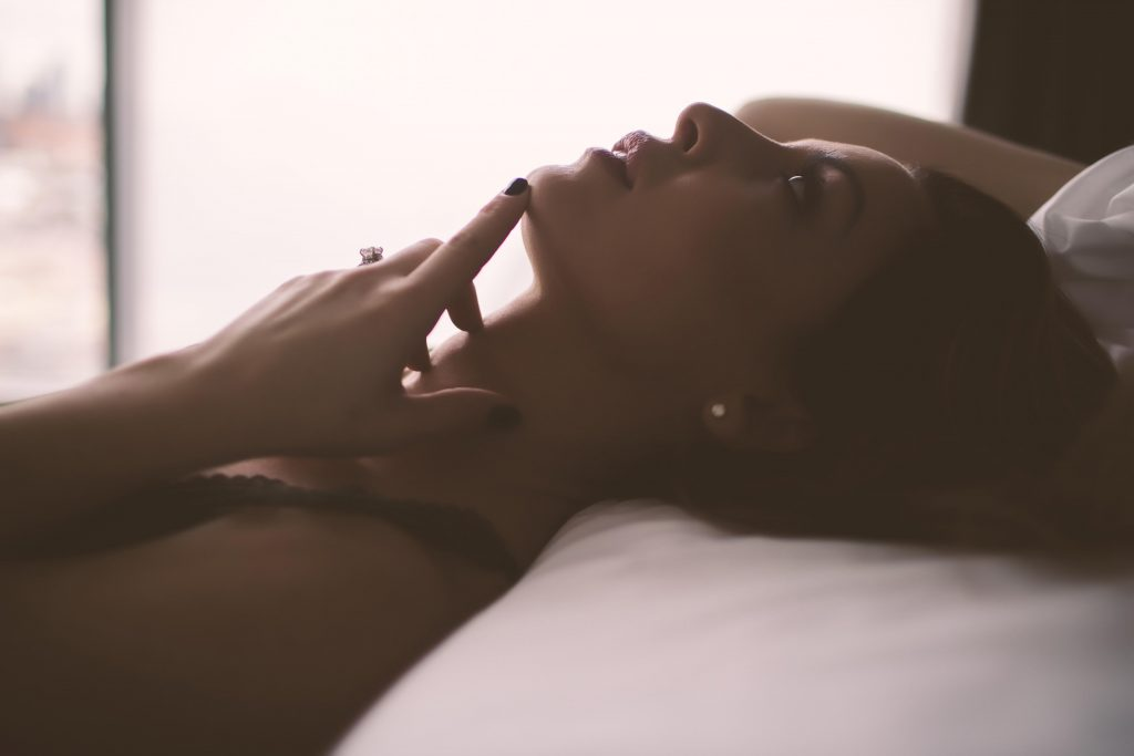 A woman posing on a bed in a thoughtful position