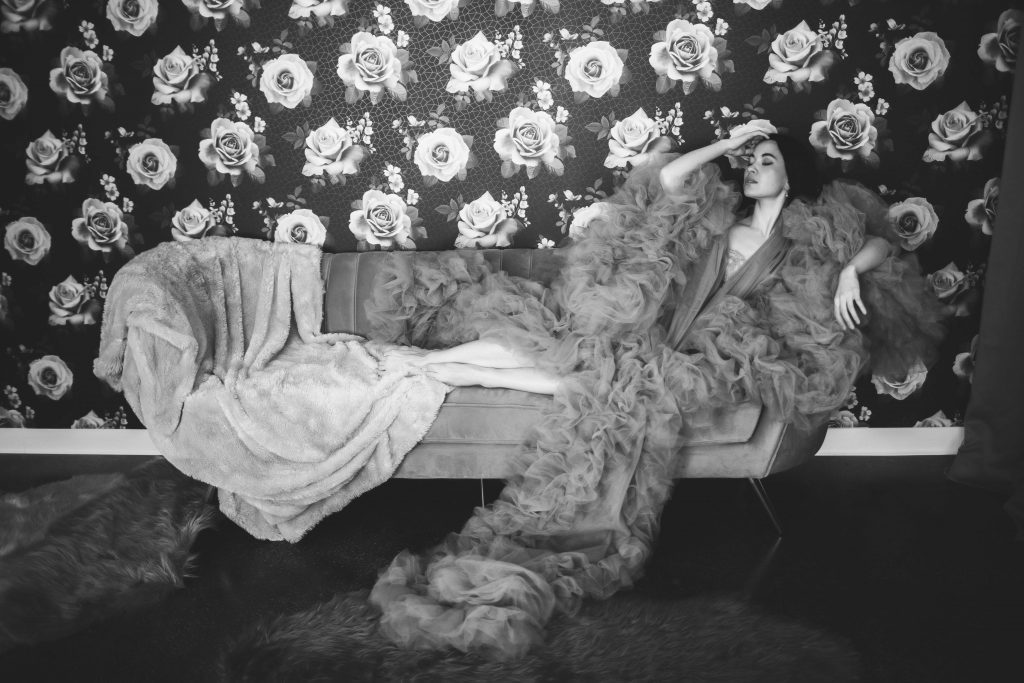 a black and white portrait of a model in a boudoir robe